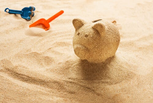 Sand piggy bank on beach